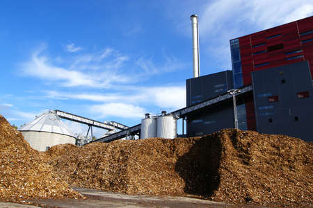 biomass: bio power plant with storage of wooden fuel against blue sky