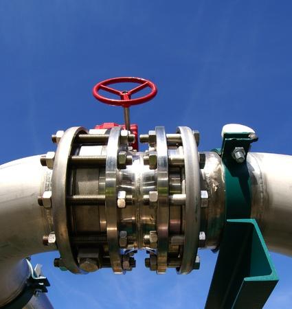 turbina de vapor: Zona industrial, tuberías de acero y válvulas contra el cielo azul