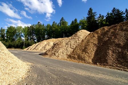 recursos naturales: almacenamiento del combustible de madera contra el cielo azul