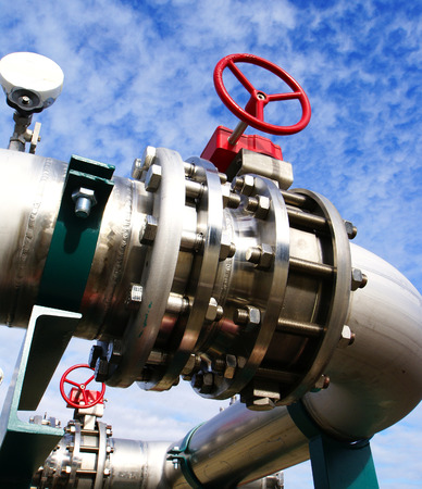 commercial equipment: Industrial zone, Steel pipelines and valves against blue sky            Stock Photo