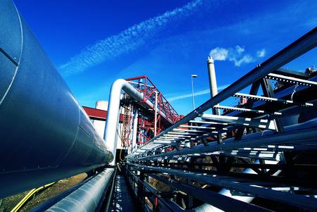 ingenieria industrial: Zona industrial, tuberías de acero y válvulas contra el cielo azul