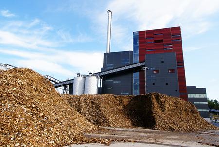 kraftwerk: Bio-Kraftwerk mit Speicherung des hölzernen Kraftstoffs (Biomasse) gegen den blauen Himmel