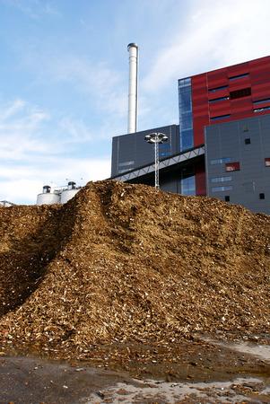 biomasa: planta de energía bio con el almacenamiento del combustible de madera (biomasa) contra el cielo azul