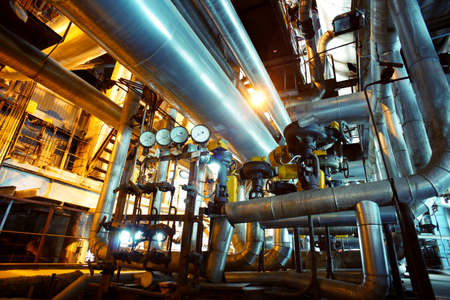 energy supply: Equipment, cables and piping as found inside of a industrial power plant Stock Photo