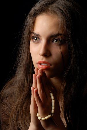 credo: Praying of repentant woman with religious string of beads Stock Photo