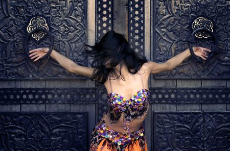 belly dancing: Photo of girl in national arabic clothes at the ancient gate Stock Photo