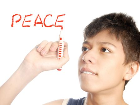 Boy writing the Peace word by the red on a white photo