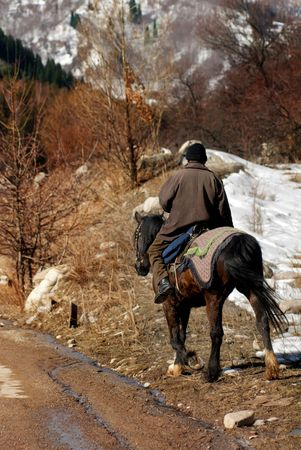 stockman: Photo of the horseman in mountain area during early spring