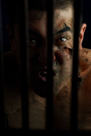 Condemned maniac with burnt skin in the cage photo
