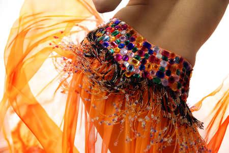 buikdansen: Buik van de vrouw dansen in het oranje dansen jurk Stockfoto