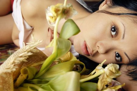 Sensual portrait of sorrowful lady laying with flowers Stock Photo - 2677778