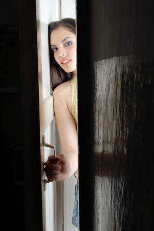 abriendo puerta: Joven ama de casa que responde a la campana y abrir la puerta  Foto de archivo