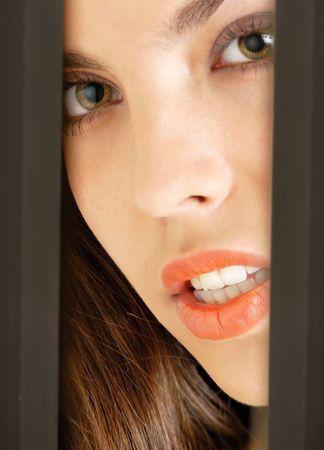 Young sexy model peeking into the door or between walls Stock Photo - 2683690