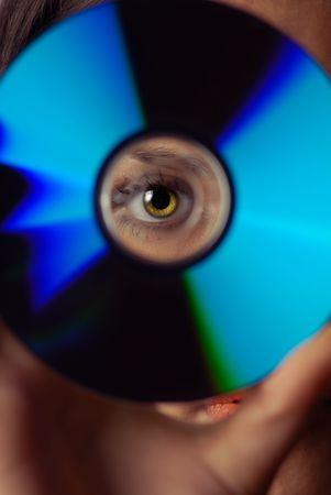 compact disk: Woman peeping through compact disk Stock Photo