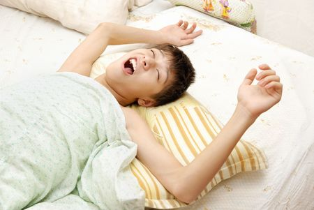 Yawning awaking boy on the bed at the early morning Stock Photo - 2689763