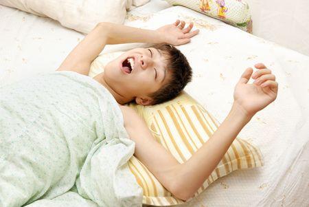 awaking: Yawning awaking boy on the bed at the early morning Stock Photo