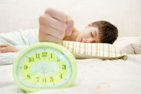 arouse: Sleeping boy hitting the alarm clock at the early morning