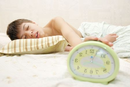 oversleep: Sleeping boy and alarm clock in the bedroom