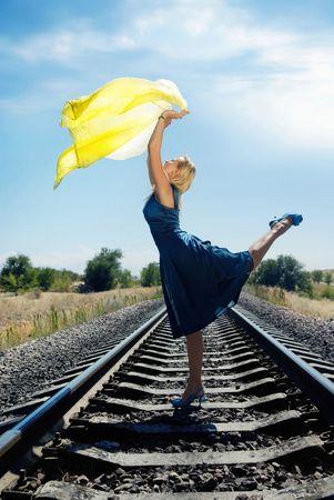 Dancing model with yellow fabric on the railway  photo