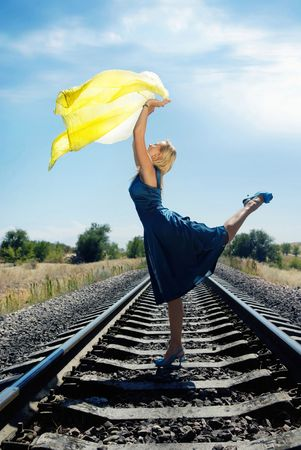 sag: Dancing model with yellow fabric on the railway