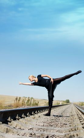 choreographic: Dancing woman on the railway as a train-barrier  Stock Photo