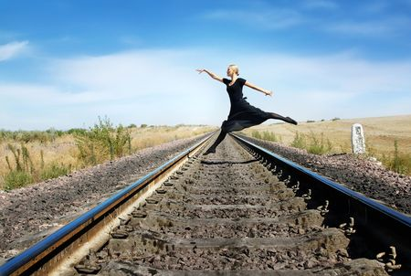 Ballet dancer jumping over the railway photo