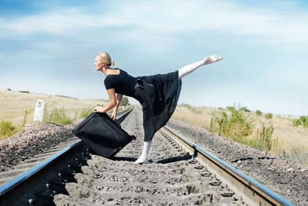 Ballet dancer with suit-case on the railway going to the travel photo