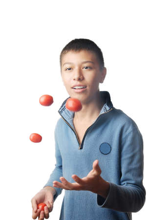 adroitness: Studio photo of the young boy juggling with tomato