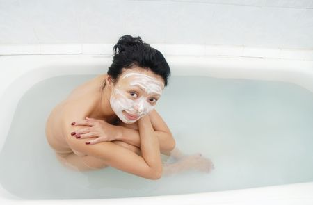 Pretty woman with beauty mask sitting in the bath photo