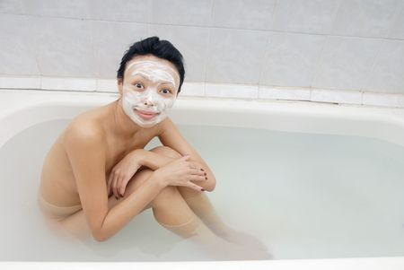 Smiling model with beauty mask sitting in the bath photo