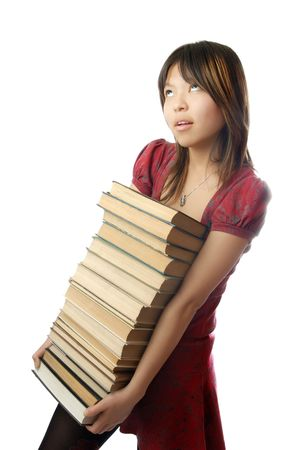 Young schoolgirl carrying numerous heavy books photo