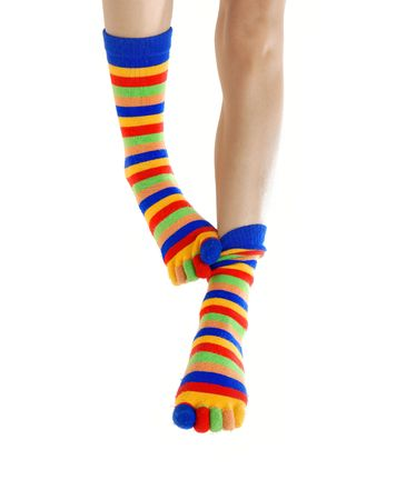 brindled: Thin legs in colored socks scratching each other Stock Photo