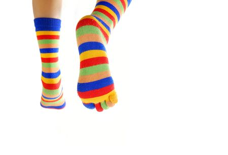 brindled: Close-up photo of the legs in colored socks going away Stock Photo