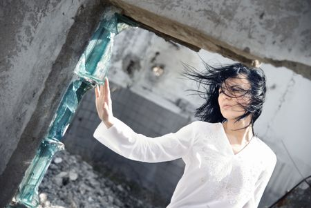 Sad woman touhcing the broken glass in the ruins of her house photo