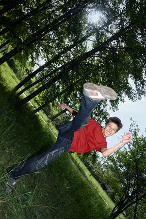karate kick: Outdoors photo of the cheerful boy doing karate kick Stock Photo