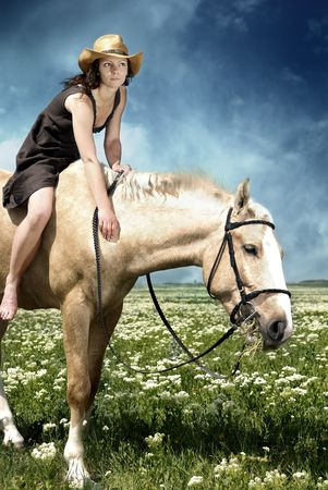Portrait of the woman feeding her horse with grass Stock Photo