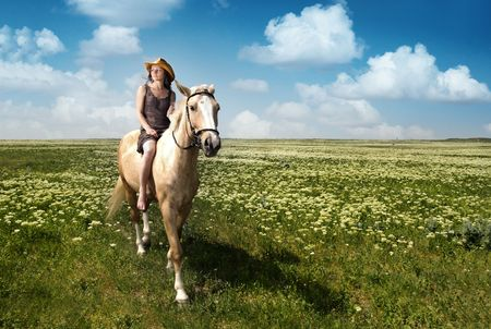 Outdoor photo of the young lady with hat riding on the horse Stock Photo