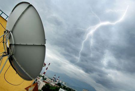 Creative photo of the high-tech parabolic antenna and lightning photo