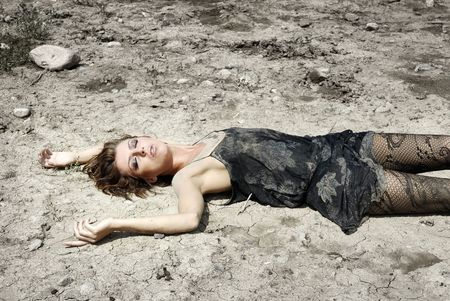 arid: Gorgeous lady with closed eyes laying on an arid ground