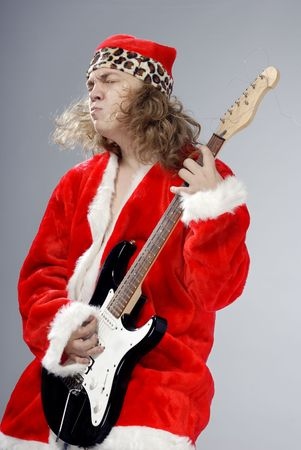 Studio photo of Santa playing the electric guitar Stock Photo - 3783921