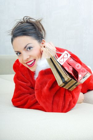 Happy smiling lady laying on a sofa with gift packages photo