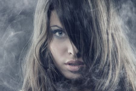 Sexy woman with long hairs in the heavy smoke