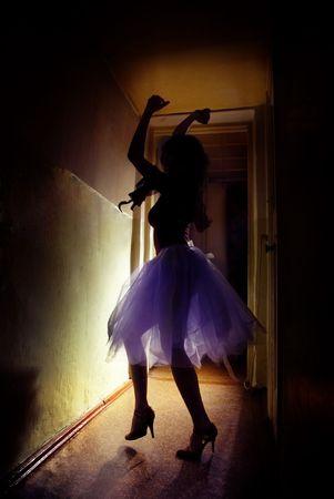 Elegant woman dancing in the dark corridor photo