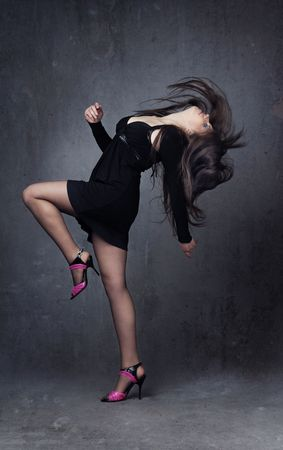 Woman dancing indoors in the stylish dress and shoes photo