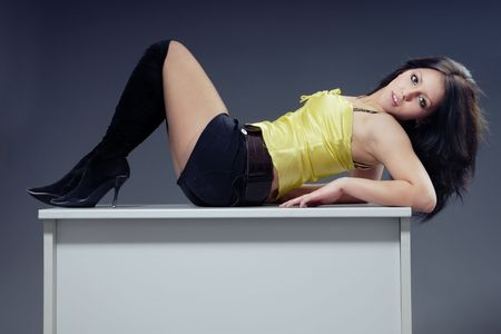 Lady in stylish clothes laying on a table photo