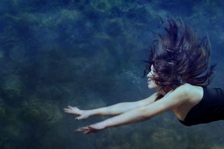 Beautiful lady swimming and diving underwater Stock Photo