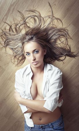 Sexy lady in jeans and white shirt laying on a parquet floor Stock Photo - 4266319