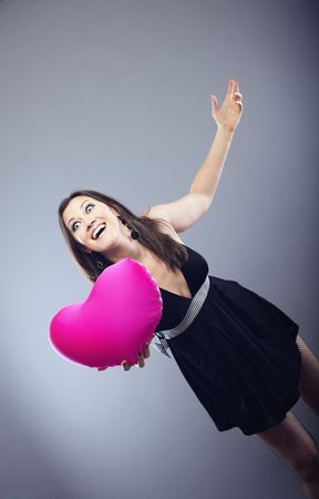 Happy laughing lady giving the Valentine heart