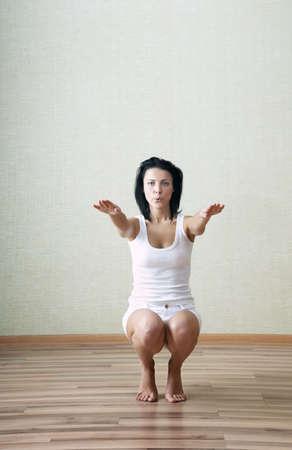 squatting: Deportiva dama haciendo cuclillas en casa