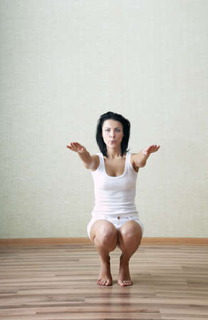 curtsy: Sportive lady doing squatting at home Stock Photo